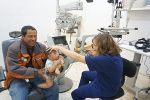 Optometrist Jen Cramer examines a young child brought to the clinic by his grandfather.