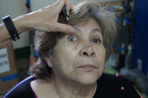 Optometrist Jen Cramer examines a woman with an eye condition