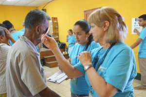 Grand Island Lion Anne Fahning performs near vision screening test on elderly man with the help of a local translator.